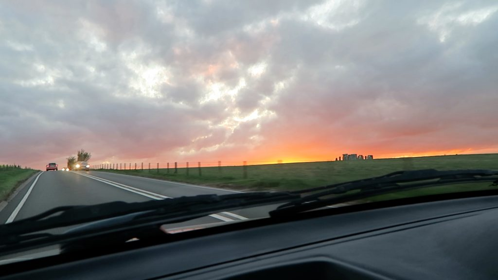 Car hire in Somerset driving past stone henge at sunset