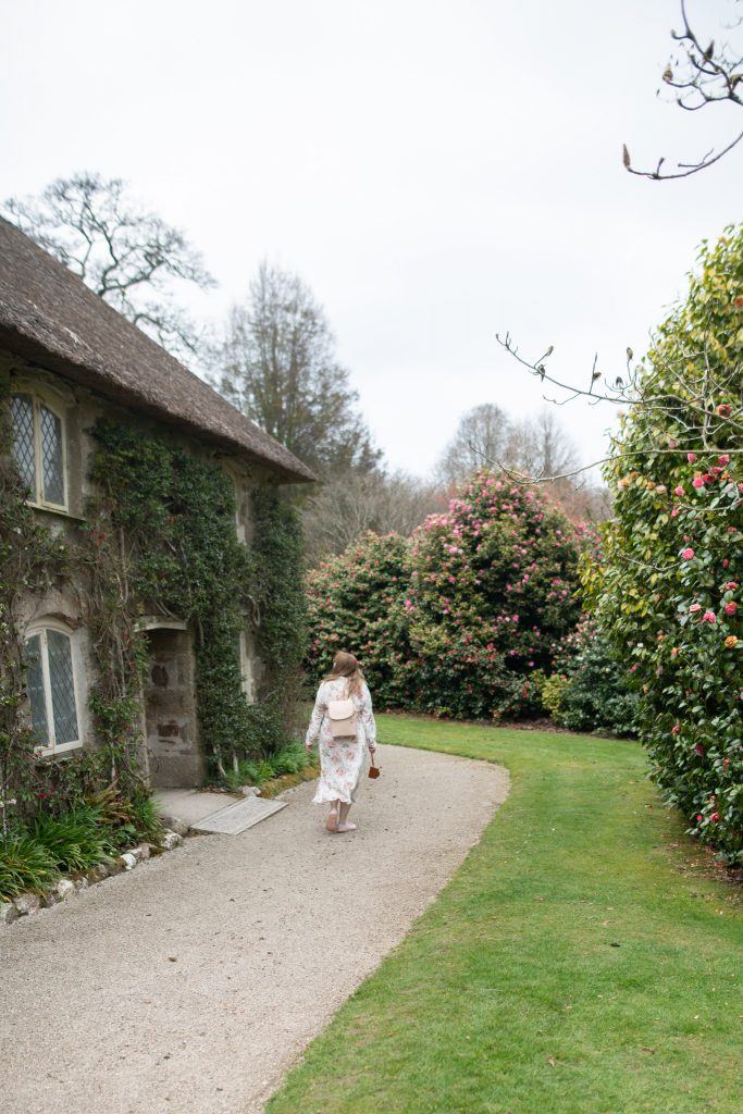 British fashion blogger exploring Lanhydrock gardens in a floral shirt dress