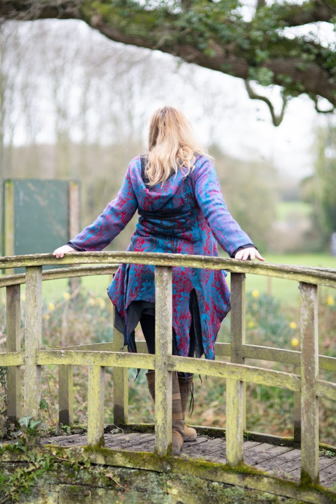 style blogger wearing a handmade pixie coat leaning on a bridge