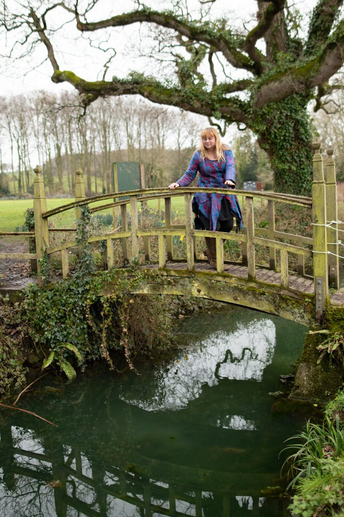 Fashion blogger over 30 wearing a pixie jacket leaning on an old bridge