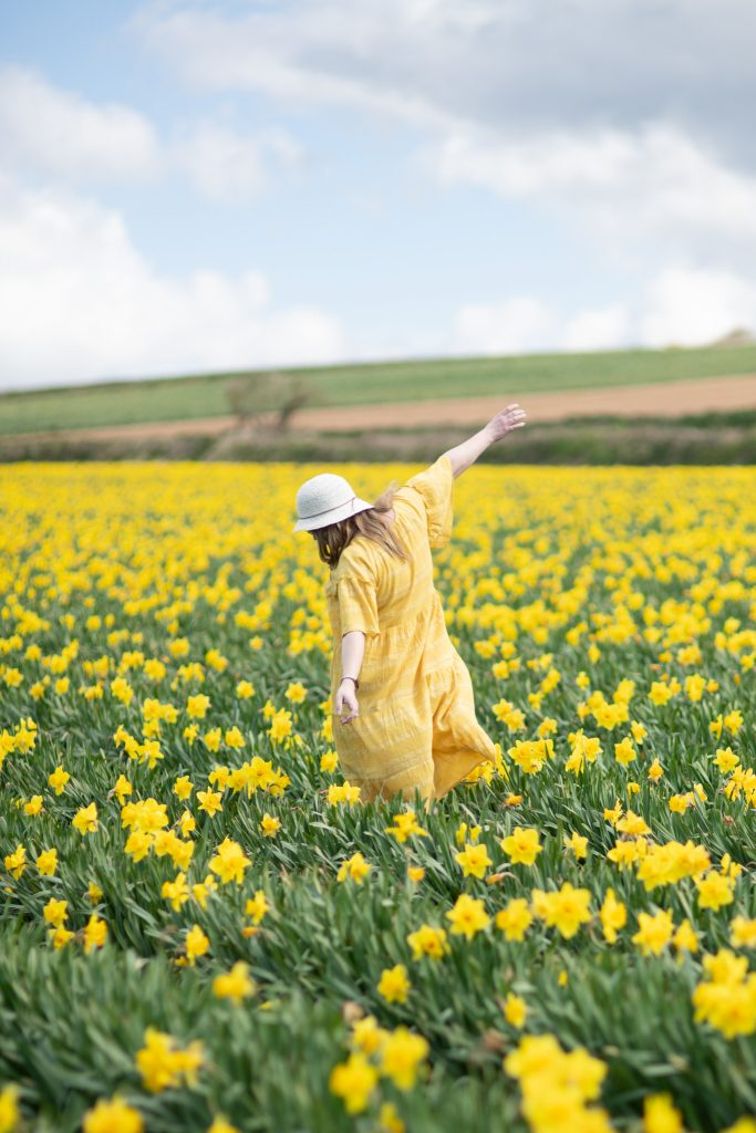 40 plus fashion blogger running through a field of daffodils in the perfect yellow dress