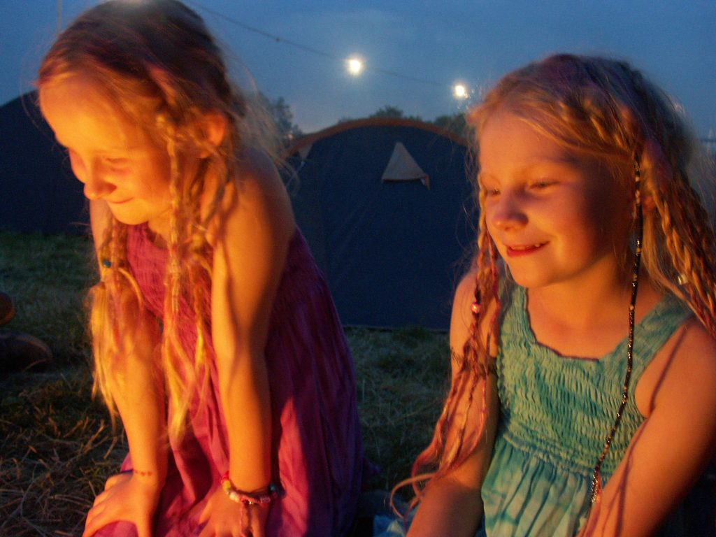children sitting by the fire at Glastonbury festival