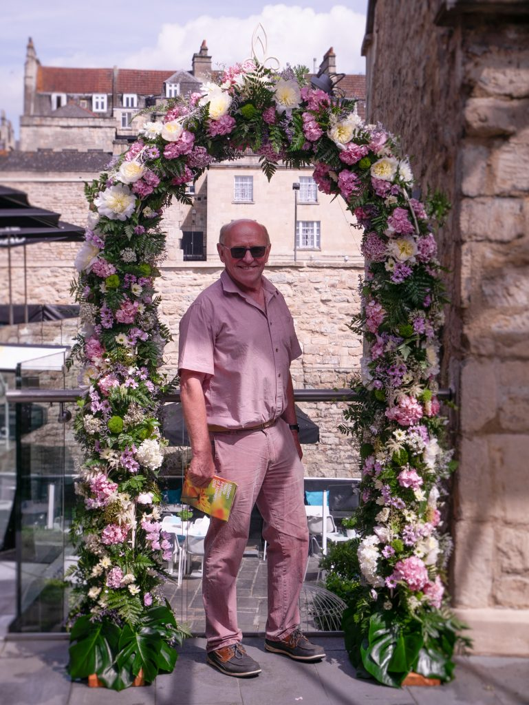 Jon Wheatley standing in floral archway for Festival of Flowers at Milsom Place in Bath