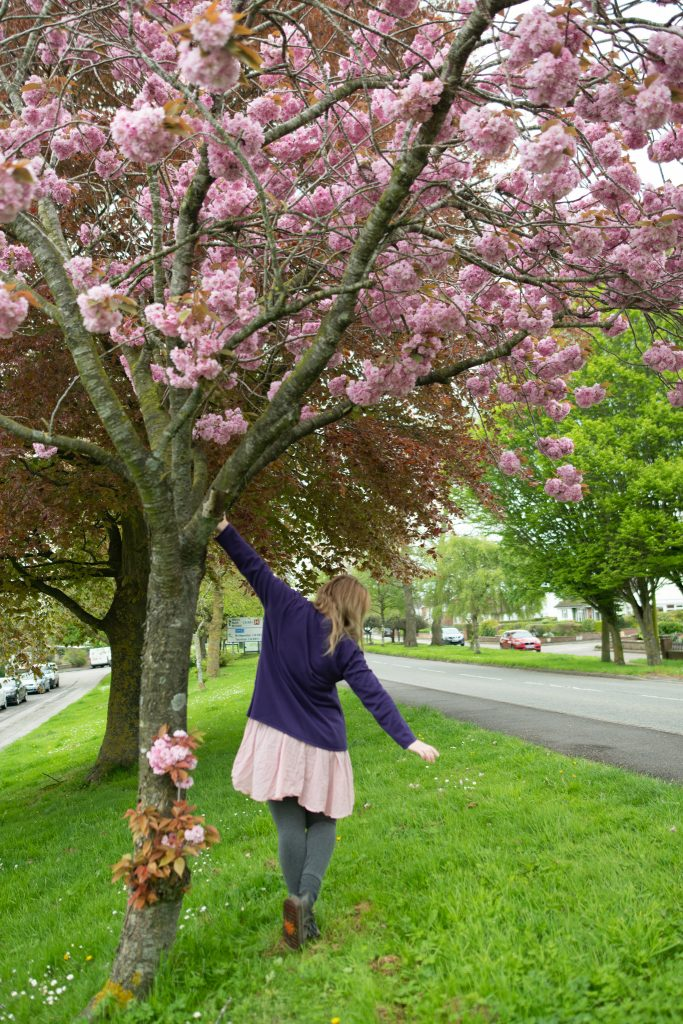Fashion blogger wearing a purple cardigan and pink dress