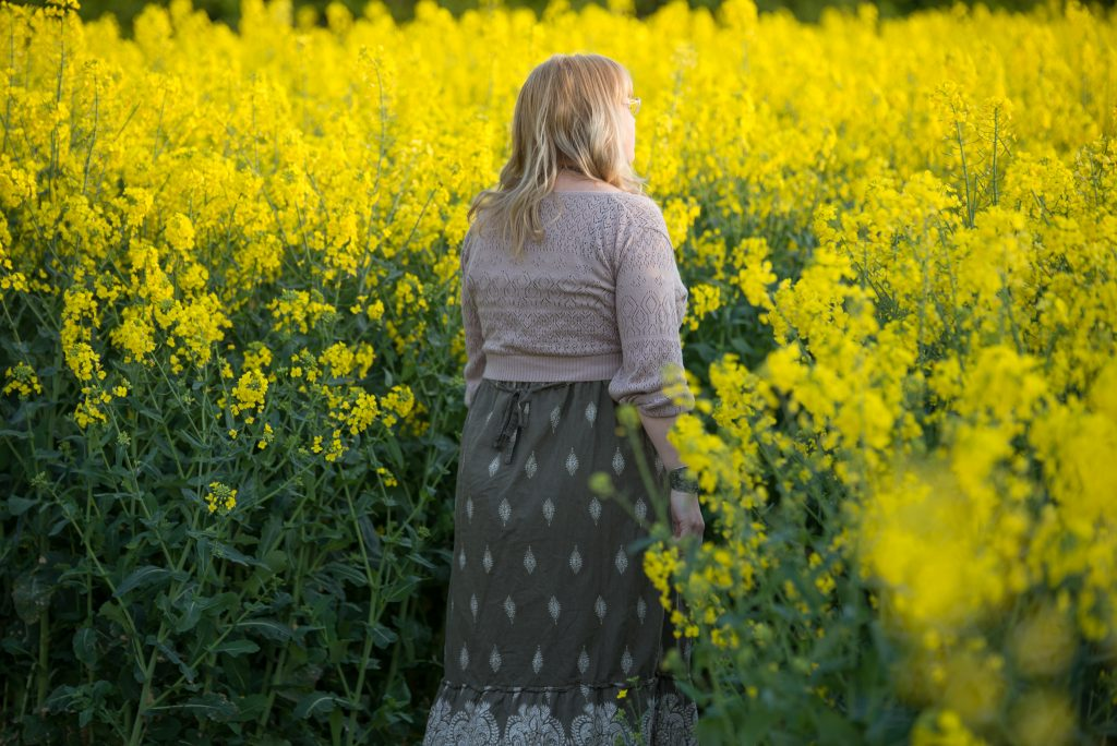 fashion blogger in a rape seed oil field wearing a boho dress