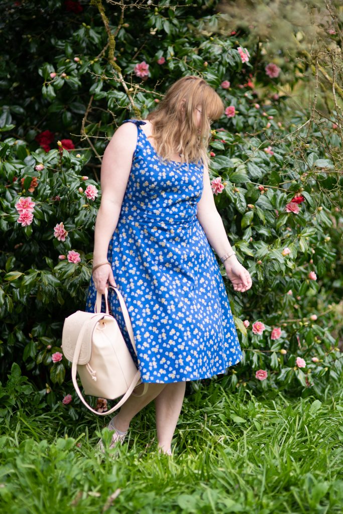 British fashion blogger over 30 wearing a blue floral summer dress