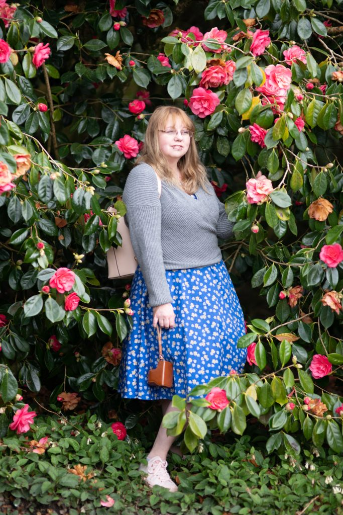 Over 40 style blogger in a camelia bush