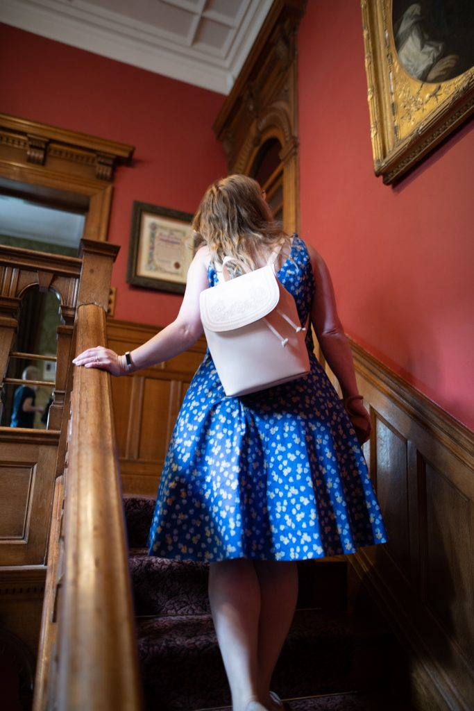 Style blogger wearing a blue floral dress & rucksack at Lanhydrock