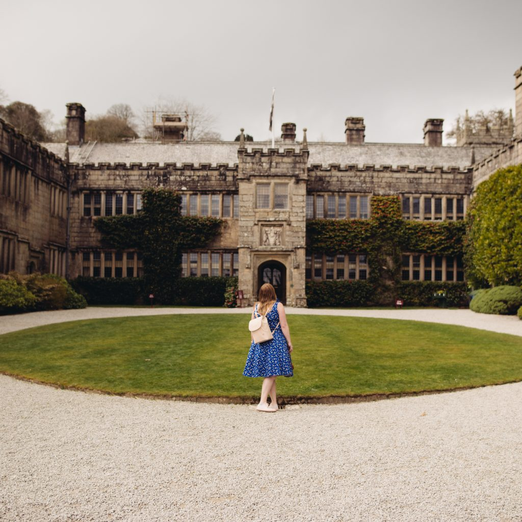 Style blogger standing in front of Lanhydrock stately home