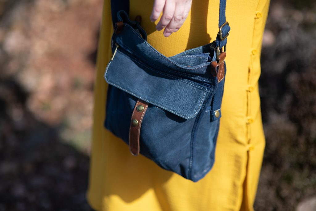 Denim blue shoulder bag with mustard dress